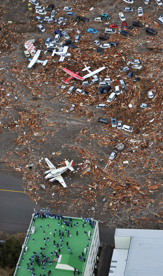 Photo - People seek refuge on the rooftop of a building as light planes and vehicles sit among the debris after they were swept by a tsumani that struck Sendai airport in northern Japan on Friday March 11, 2022. A magnitude 8.9 earthquake slammed Japan's eastern coast Friday, unleashing a 13-foot (4-meter) tsunami that swept boats, cars, buildings and tons of debris miles inland.  (AP Photo/Kyodo News) JAPAN OUT, MANDATORY CREDIT, FOR COMMERCIAL USE ONLY IN NORTH AMERICA ORG XMIT: TOK837