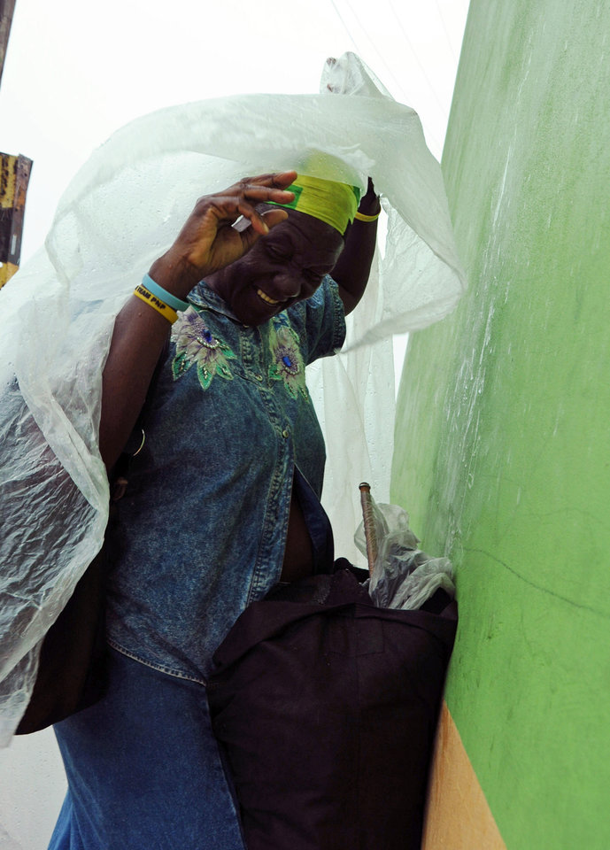 Photo -   Pauline Daley covers herself as rain brought by the outer bands of Tropical Storm Sandy falls in Kingston, Jamaica, Tuesday, Oct. 23, 2012. The U.S. National Hurricane Center in Miami said Sandy was expected to become a hurricane as it nears Jamaica on Wednesday. (AP Photo/Collin Reid)
