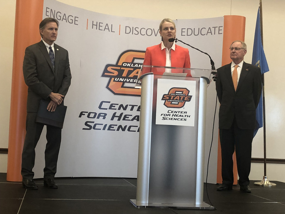 Photo - Dr.  Kayse Shrum talks about $270 million settlement with Purdue Pharma, $200 million to establish endowment for OSU Center for Wellness and Recovery. Also pictured, Oklahoma Attorney General Mike Hunter is on the left, OSU president Burns Hargis is on the right.
