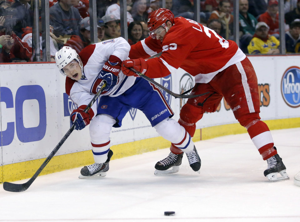 Photo - Detroit Red Wings' Brian Lashoff, right, shoves Montreal Canadiens' Brendan Gallagher (11) off the puck during the second period of an NHL hockey game Thursday, March 27, 2014, in Detroit. (AP Photo/Duane Burleson)