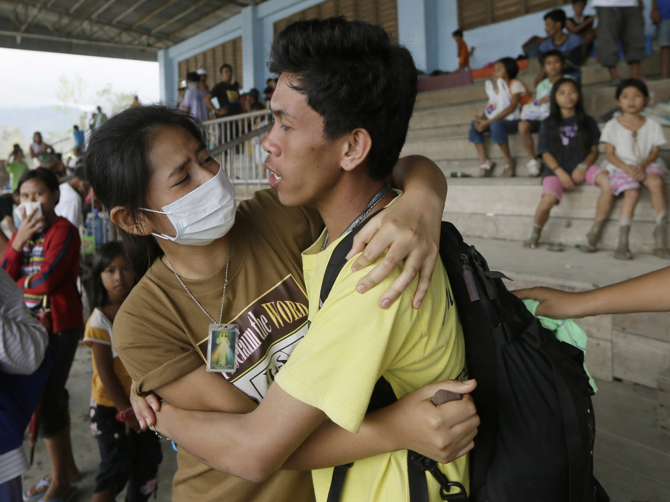Two friends are reunited by chance while waiting to receive relief goods following the visit of Philippine President Benigno Aquino III at New Bataan township, Compostela Valley in southern Philippines Friday Dec. 7, 2012. More than 310,000 people have lost their homes since Typhoon Bopha struck Tuesday and are crowded inside evacuation centers or staying with their relatives, relying on food and emergency supplies being rushed in by government agencies and aid groups. (AP Photo/Bullit Marquez)