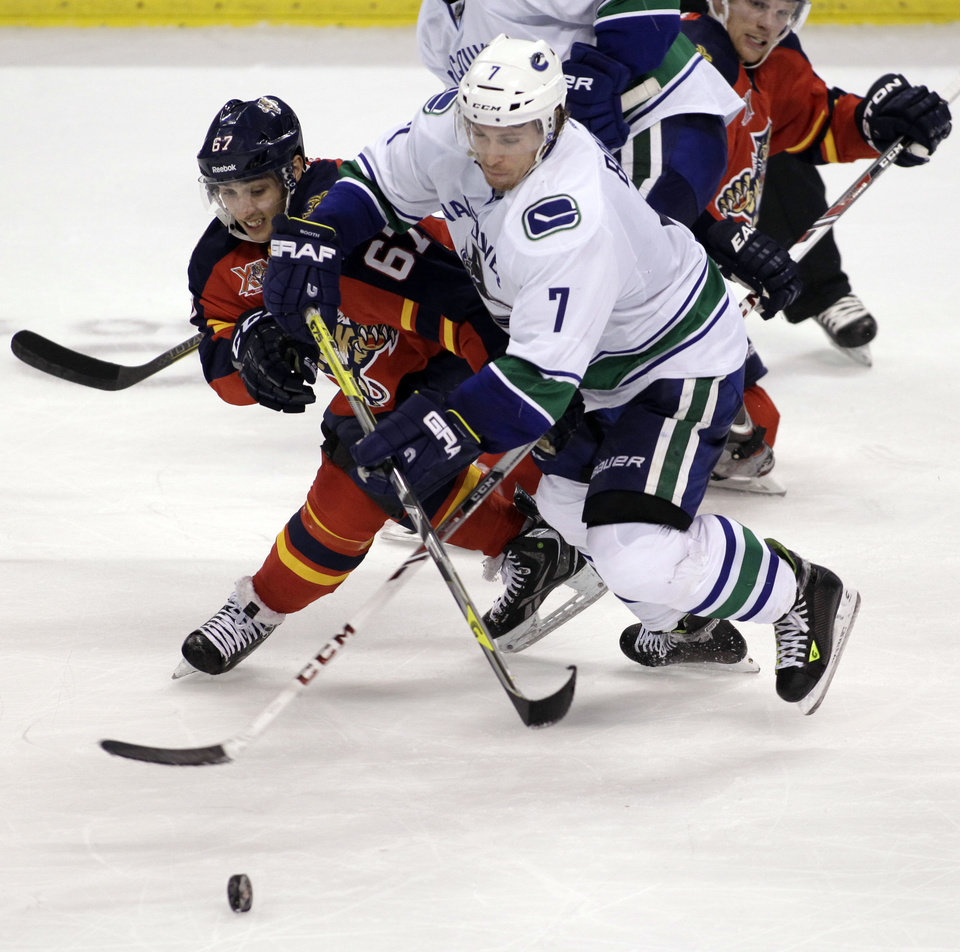 Photo - Florida Panthers' Vincent Trocheck (67) and Vancouver Canucks' David Booth (7) battle for control of the puck during the second period of an NHL hockey game on Sunday, March 16, 2014, in Sunrise, Fla. (AP Photo/Luis M. Alvarez)