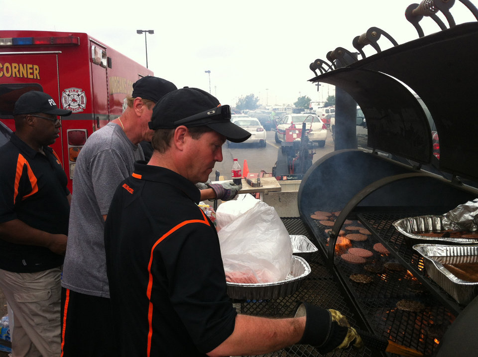 Photo - OSU basketball coach Travis Ford helps cook hamburgers in the parking lot of the Home Depot in Moore on Friday. PHOTO BY BERRY TRAMEL, THE OKLAHOMAN KOD