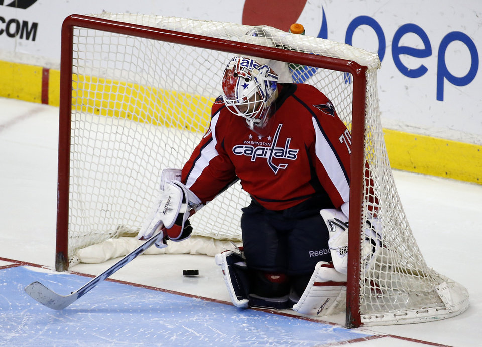 Photo - Washington Capitals goalie Braden Holtby pauses in the goal with the puck after the game-winning goal by Tampa Bay Lightning defenseman Matt Carle in the shootout portion of an NHL hockey game, Sunday, April 13, 2014, in Washington. The Lightning won 1-0. (AP Photo/Alex Brandon)
