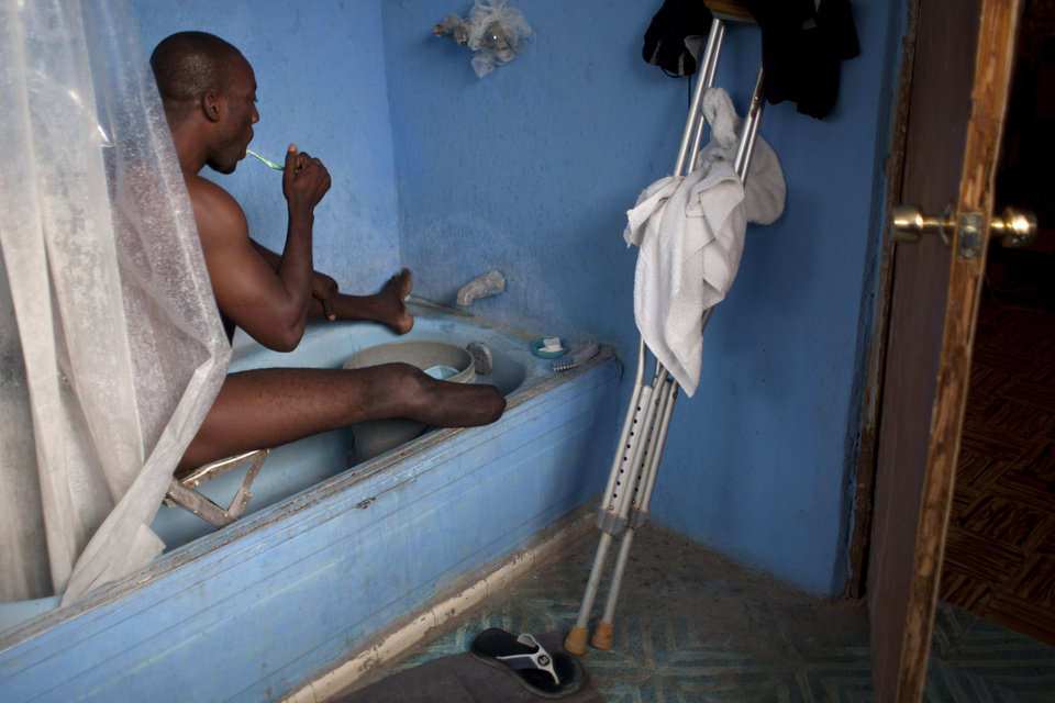 Photo - In this Jan. 18, 2013 photo, professional dancer Georges Exantus bathes as he prepares for a concert in Port-au-Prince, Haiti.  Exantus thought he'd never dance again. The earthquake three years ago in Haiti's capital flattened the apartment where he was living, where he spent three days trapped under a heap of jagged rubble. After friends dug him out, doctors amputated his right leg just below the knee. If some see him as something of an outcast, his friends find inspiration: He's not one for self-pity; he was determined to dance again, and did. He's part of a Latin dance company and gives classes. (AP Photo/Dieu Nalio Chery)