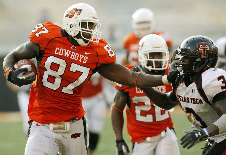 Photo - OSU's Brandon Pettigrew (87) stiff arms Jamar Wall (3) Texas Tech on his way to a touchdown in the fourth quarter of the college football game between the Oklahoma State University Cowboys (OSU) and the Texas Tech University Red Raiders (TTU) at Boone Pickens Stadium in Stillwater, Okla., on Saturday, Sept. 22, 2007. OSU won, 49-45. By NATE BILLINGS, The Oklahoman