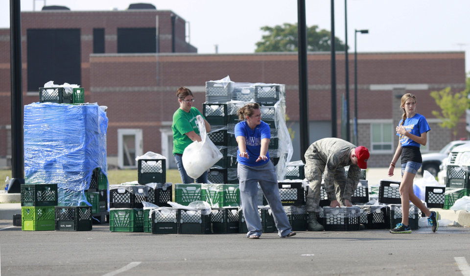 Photo - Volunteers coordinate a fresh drinking water distribution point, Sunday, Aug. 3, 2014, at Woodward High School in Toledo, Ohio. More tests are needed to ensure that toxins are out of Toledo's water supply, the mayor said Sunday, instructing the 400,000 people in the region to avoid drinking tap water for a second day. Toledo officials issued the warning early Saturday after tests at one treatment plant showed two sample readings for microsystin above the standard for consumption, possibly because of algae on Lake Erie. (AP Photo/Haraz N. Ghanbari)