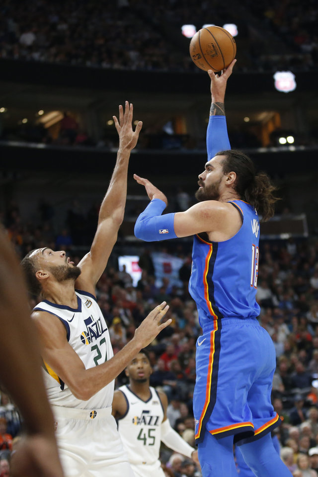 Photo - Oklahoma City Thunder center Steven Adams, right, shoots as Utah Jazz center Rudy Gobert (27) defends during the first half of an NBA basketball game Wednesday, Oct. 23, 2019, in Salt Lake City. (AP Photo/Rick Bowmer)