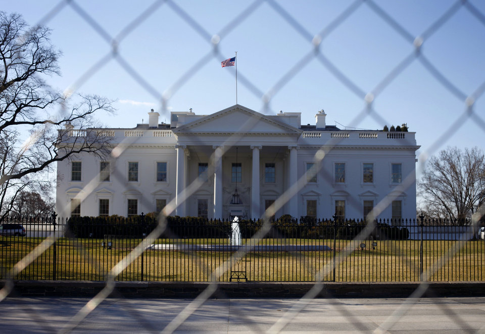 In this March 4, 2013, photo, The White House is seen through a chain-link fence where the inaugural reviewing stand once stood in Washington. Automatic spending cuts that took effect last Friday are expected to touch a vast range of government services. The Obama administration is canceling tours of the White House beginning Saturday, March 9, citing staffing reductions prompted by automatic budget cuts that began to take effect last Friday.  (AP Photo/Pablo Martinez Monsivais)