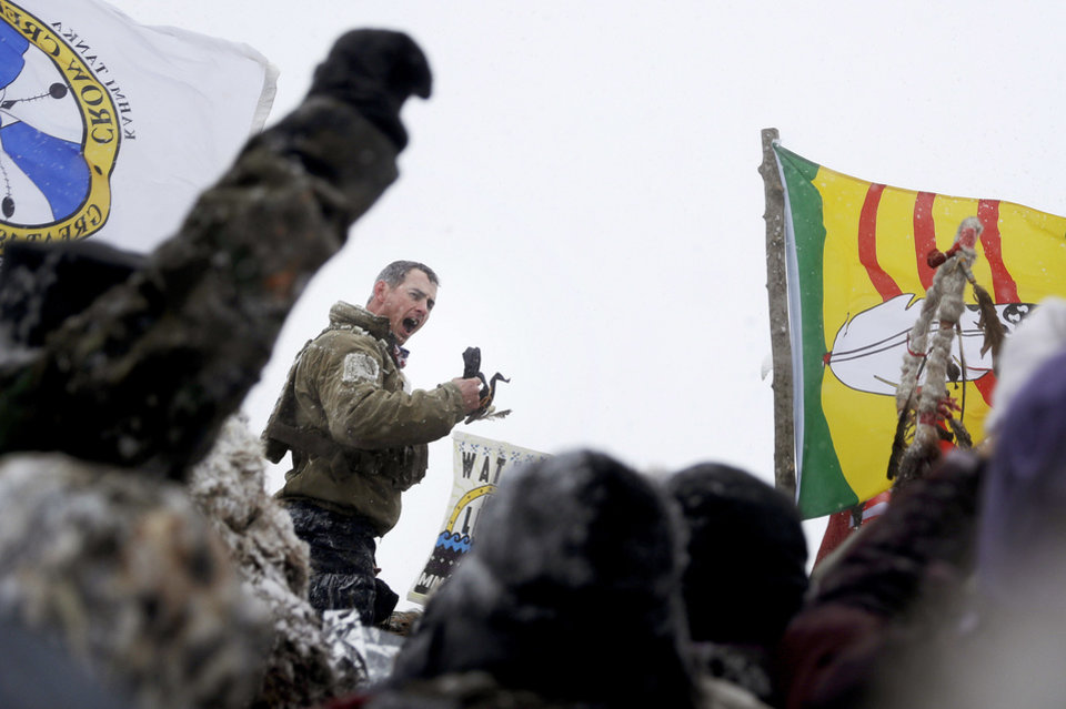 Photo - United States Navy veteran Kash Jackson speaks during a march with fellow veterans and Native American to a closed bridge outside the Oceti Sakowin camp where people have gathered to protest the Dakota Access oil pipeline in Cannon Ball, N.D., Monday, Dec. 5, 2016. (AP Photo/David Goldman)