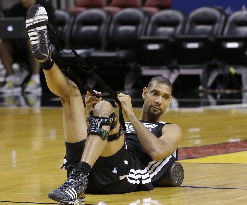 Photo - San Antonio Spurs power forward Tim Duncan stretches during NBA basketball practice, Wednesday, June 19, 2013, at the American Airlines Arena in Miami. The Spurs take on the Miami Heat in Game 7 of the NBA Finals on Thursday in Miami. (AP Photo/Wilfredo Lee)