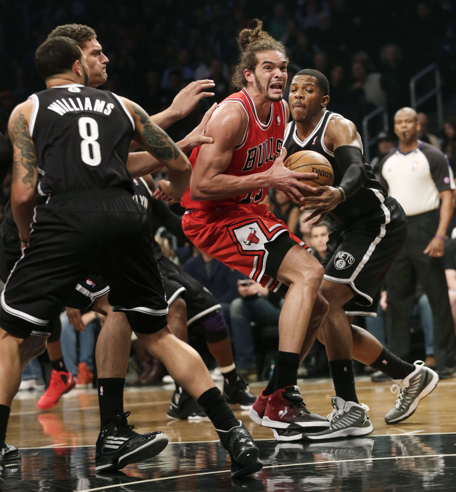 Photo - Chicago Bulls' Joakim Noah, second from right, tries to get through Brooklyn Nets defense, including Joe Johnson, right, during the first quarter of Game 1 of a first-round series of the NBA basketball playoffs, Saturday, April 20, 2013, in New York. (AP Photo/Seth Wenig)