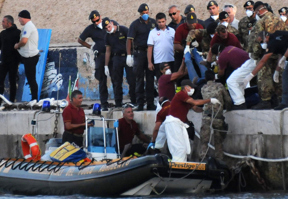 Photo - Rescuers lift a body as they reach the port of Lampedusa, southern Italy, Thursday, Oct. 3, 2013. At least 114 people died and scores more were missing late Thursday after a crowded fishing boat carrying African migrants from Tripoli caught fire, flipped over and sank, Italian officials said. Between 450 and 500 people were believed to be on board; health commissioner Antonio Candela said only 159 were rescued. (AP Photo/Danilo Taralli)