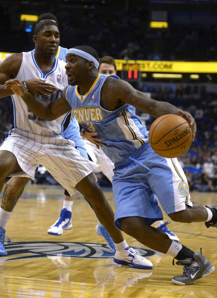 Denver Nuggets guard Ty Lawson, right, drives past Orlando Magic guard E'Twaun Moore during the first half of an NBA basketball game in Orlando, Fla., Friday, Nov. 2, 2012. (AP Photo/Phelan M. Ebenhack)