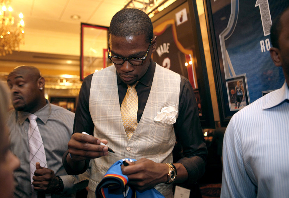 Photo - Oklahoma City Thunder's Kevin Durant signs an autograph during the KD 35 Ball benefiting the Kevin Durant Family Foundation at the Skirvin Hilton Hotel in Oklahoma City, Saturday, March 31, 2012. (AP Photo/The Oklahoman, Sarah Phipps) ORG XMIT: OKOKL103