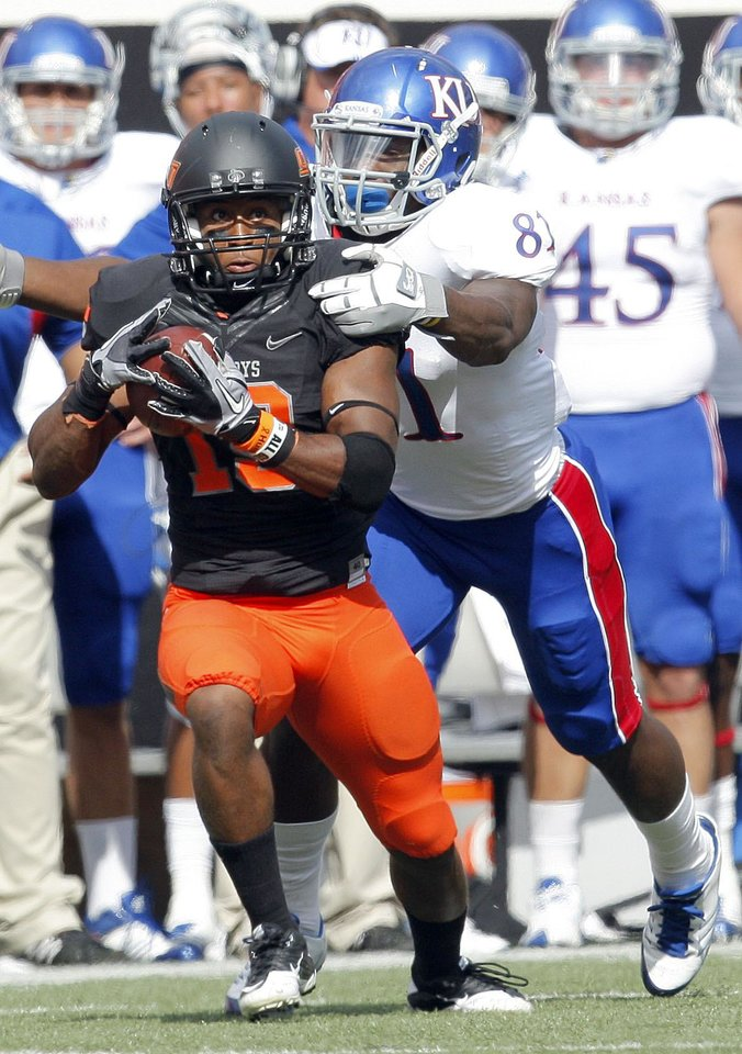 Photo - Oklahoma State's Brodrick Brown (19) intercepts a pass intended for Kansas' Marquis Jackson (81) during the first half of the college football game between the Oklahoma State University Cowboys (OSU) and the University of Kansas Jayhawks (KU) at Boone Pickens Stadium in Stillwater, Okla., Saturday, Oct. 8, 2011. Photo by Sarah Phipps, The Oklahoman