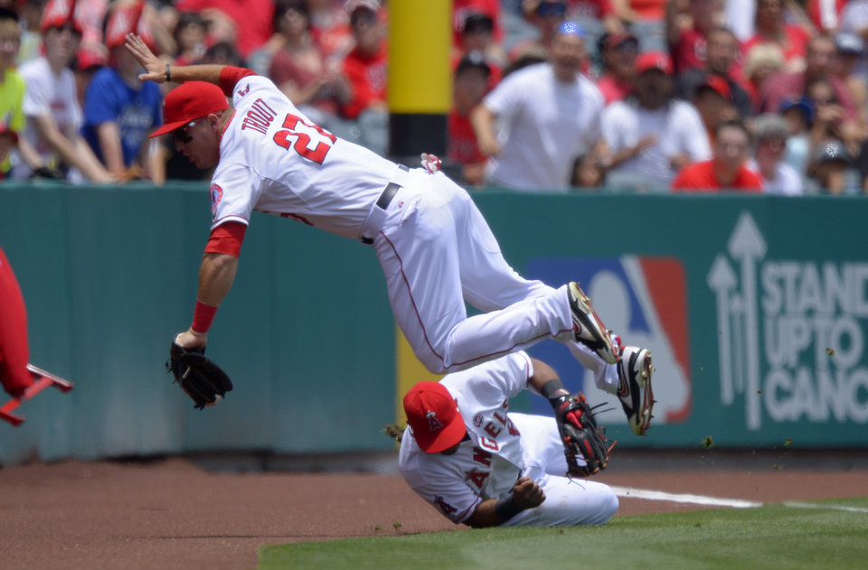 Photo - Los Angeles Angels center fielder Mike Trout, top, trips over third baseman Alberto Callaspo as they try to get a foul ball hit by Pittsburgh Pirates' Pedro Alvarez during the first inning of their baseball game on Sunday, June 23, 2013, in Anaheim, Calif. Alvarez was safe on the play. (AP Photo/Mark J. Terrill)