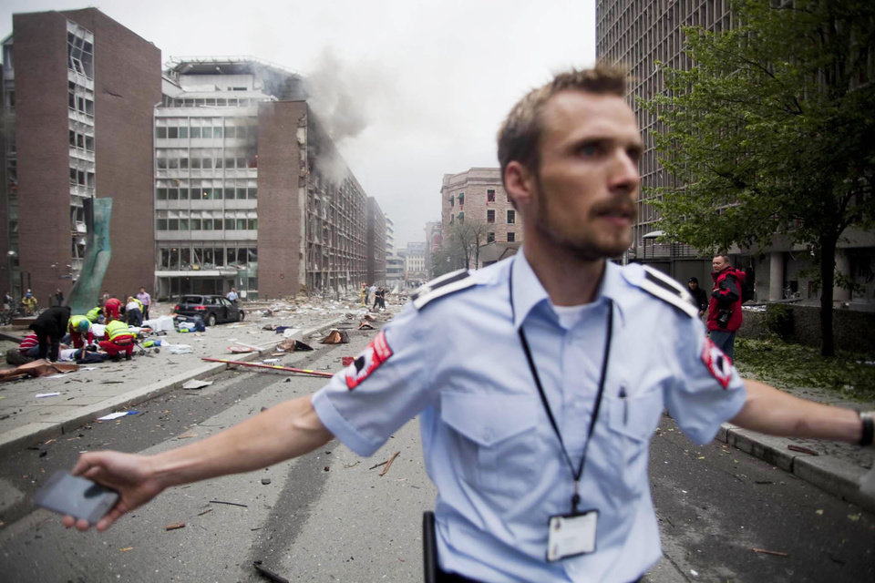 An official attempts to clear away spectators from buildings in the centre of Oslo, Friday July 22, 2011, following an explosion that tore open several buildings including the prime minister's office, shattering windows and covering the street with documents.(AP Photo/Fartein Rudjord) NORWAY OUT: ORG XMIT: LON860