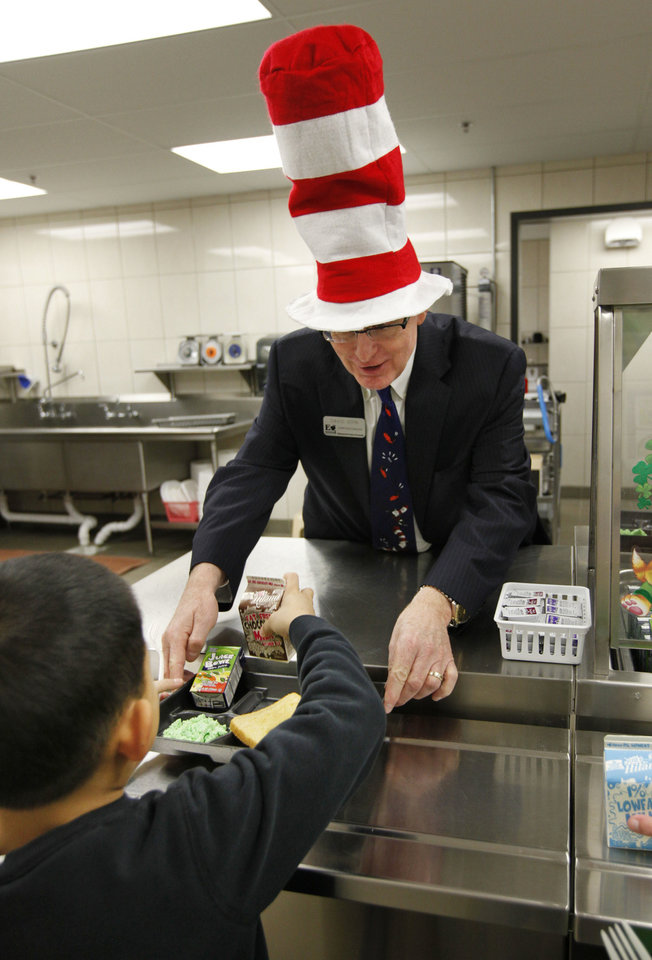 Photo - Edmond Public Schools Superintendent  David Goin serves green eggs and ham to first-graders at Clegern Elementary School in honor of Dr. Seuss' birthday. PHOTO BY PAUL HELLSTERN, THE OKLAHOMAN.  PAUL HELLSTERN - Oklahoman
