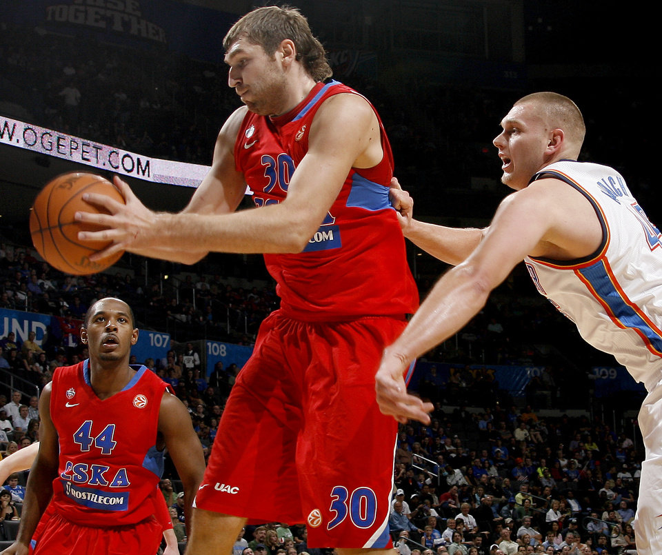 Photo - Oklahoma City's Cole Aldrich (45) tries for the ball behind CSKA Moscow's  Dmitry Sokolov (30), center, and Jamont  Gordon (44) during the preseason NBA basketball game between the Oklahoma City Thunder an CSKA Moscow in Oklahoma City, Thursday, October 14, 2010. Photo by Bryan Terry, The Oklahoman