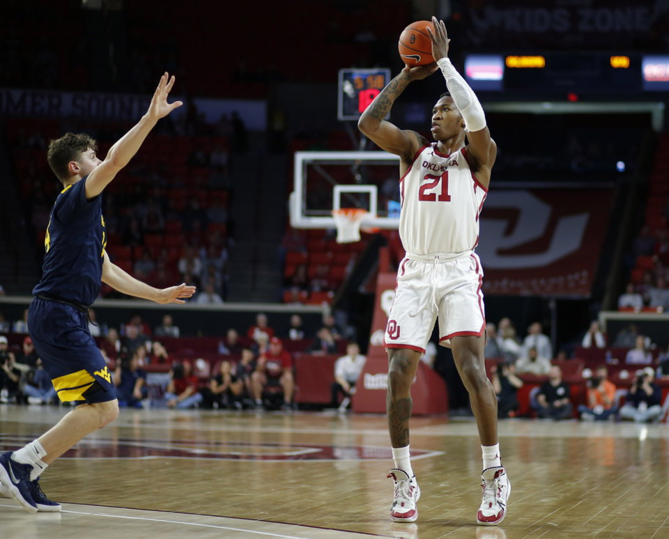 Photo - Oklahoma's Kristian Doolittle (21) shoots basket beside West Virginia's Chase Harler (14) during an NCAA mens college basketball game between the University of Oklahoma Sooners (OU) and the West Virginia Mountaineers at the Lloyd Noble Center in Norman, Okla.,Saturday, Feb. 8, 2020. [Bryan Terry/The Oklahoman]