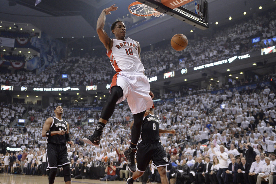 Photo - Toronto Raptors' DeMar DeRozan (10) dunks as Brooklyn Nets' Paul Pierce (34) and Deron Williams (8) look on during the first half of Game 5 of the opening-round NBA basketball playoff series in Toronto, Wednesday, April 30, 2014. (AP Photo/The Canadian Press, Frank Gunn)