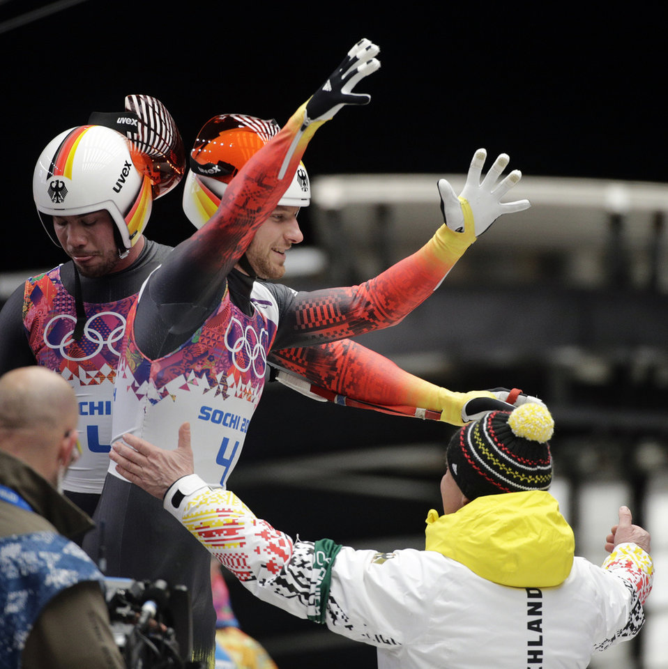 Photo - The doubles team of Tobias Wendl and Tobias Arlt from Germany celebrate in the finish area after their final run to win the gold medal during the men's doubles luge at the 2014 Winter Olympics, Wednesday, Feb. 12, 2014, in Krasnaya Polyana, Russia. (AP Photo/Jae C. Hong)