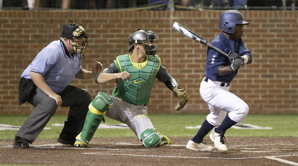 Photo - Vanderbilt's Ro Coleman hits a pinch-hit single with the bases loaded in the bottom of the ninth inning to drive in the winning run and give Vanderbilt a 3-2 win over Oregon in an NCAA college baseball regional tournament game Sunday, June 1, 2014, in Nashville, Tenn. Catching for Oregon is Jack Kruger. (AP Photo/Mark Humphrey)