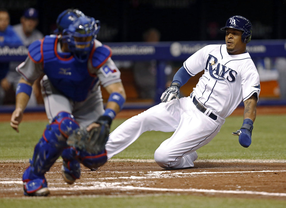 Photo - Tampa Bay Rays' Desmond Jennings slides in safely behind Texas Rangers catcher J.P. Arencibia to score on a single by Wil Myers during the fourth inning of a baseball game Friday, April 4, 2014, in St. Petersburg, Fla. (AP Photo/Mike Carlson)