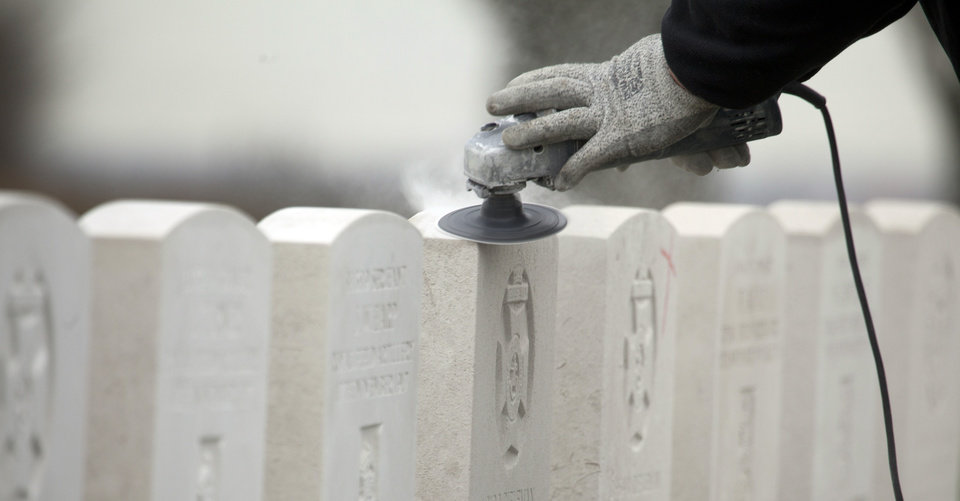 Photo - A worker for the Commonwealth War Graves Commission sands down headstones of WWI soldiers at Tyne Cot cemetery in Zonnebeke, Belgium on Monday, April 15, 2013. With nearly 12,000 graves the cemetery is the largest Commonwealth war cemetery in the world in terms of burials. Commonwealth cemeteries and monuments around the world are currently being renovated in preparation for centenary events which begin in 2014. (AP Photo/Virginia Mayo)