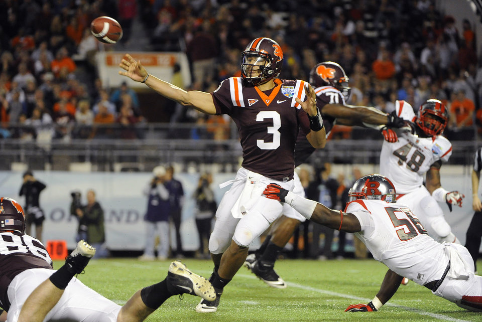 Virginia Tech quarterback Logan Thomas, center, throws to an open receiver while under pressure from Rutgers defensive end Marvin Booker, bottom right, during the second quarter of an NCAA college football Russell Athletic Bowl game on Friday, Dec. 28, 2012, in Orlando, Fla. (AP Photo/Brian Blanco)
