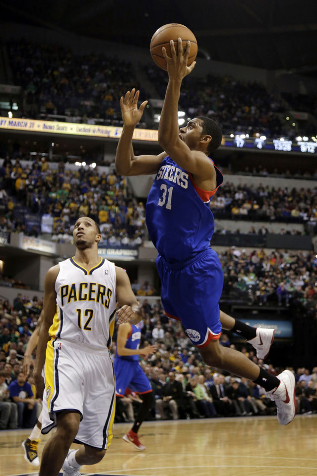 Photo - Philadelphia 76ers guard Hollis Thompson (31) shoots in front of Indiana Pacers forward Evan Turner (12) during the first half of an NBA basketball game in Indianapolis, Monday, March 17, 2014. (AP Photo/AJ Mast)
