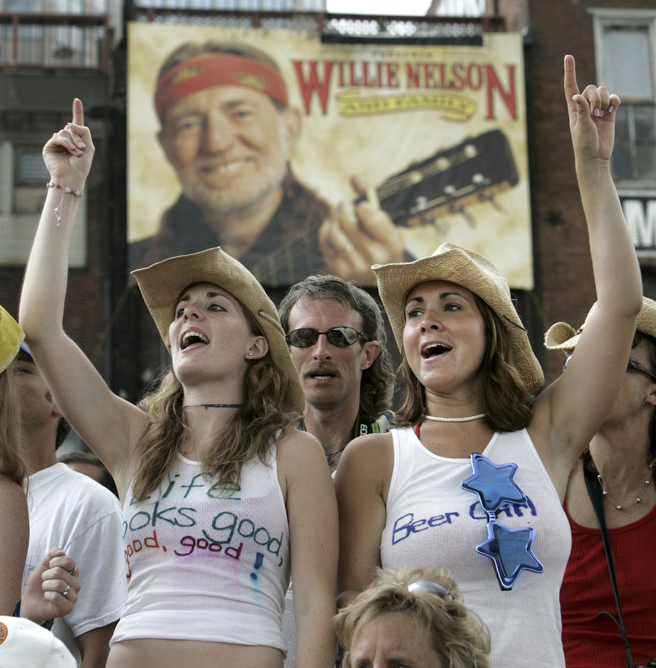 Photo - FILE -- This June 9, 2005 file photo shows Lana Deptula, left, of Crofton, Md., and Lara Wittstadt, right, of Westminster, Md., singing along at a CMA Music Festival concert in Nashville, Tenn. One of the city's biggest parties is the annual CMA Festival, and free daytime concerts are offered. (AP Photo/Mark Humphrey, File)