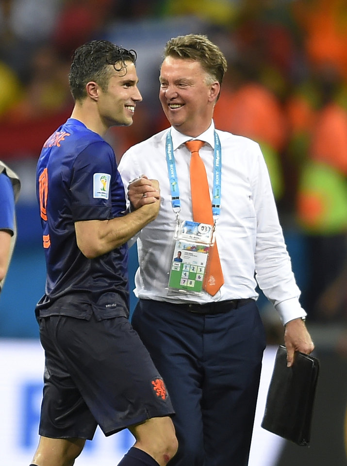 Photo - Netherlands' Robin van Persie, left, celebrates with Netherlands' head coach Louis van Gaal after the group B World Cup soccer match between Spain and the Netherlands at the Arena Ponte Nova in Salvador, Brazil, Friday, June 13, 2014. The Netherlands won the match 5-1. (AP Photo/Manu Fernandez)