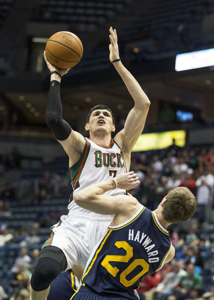 Milwaukee Bucks' Ersan Ilyasova, left, shoots over Utah Jazz Gordon Hayward during the first half of an NBA basketball game Monday, March 3, 2014, in Milwaukee. (AP Photo/Tom Lynn)