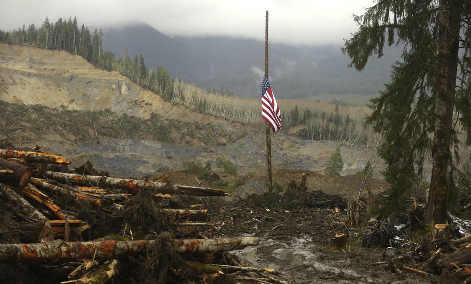 Photo - A flag flies at half-staff on a log Sunday, March 30, 2014, with the slope of the massive mudslide that struck Saturday, March 22, 2014 in the background. The search for victims of the deadly slide continued Sunday, with crews searching both with heavy machinery and by hand. (AP Photo/Ted S. Warren)