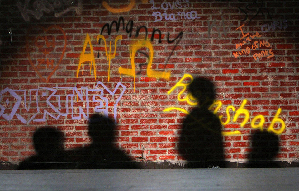 Camp participants� shadows appear on the back wall of the stage as they rehearse for a play during the summer arts program.