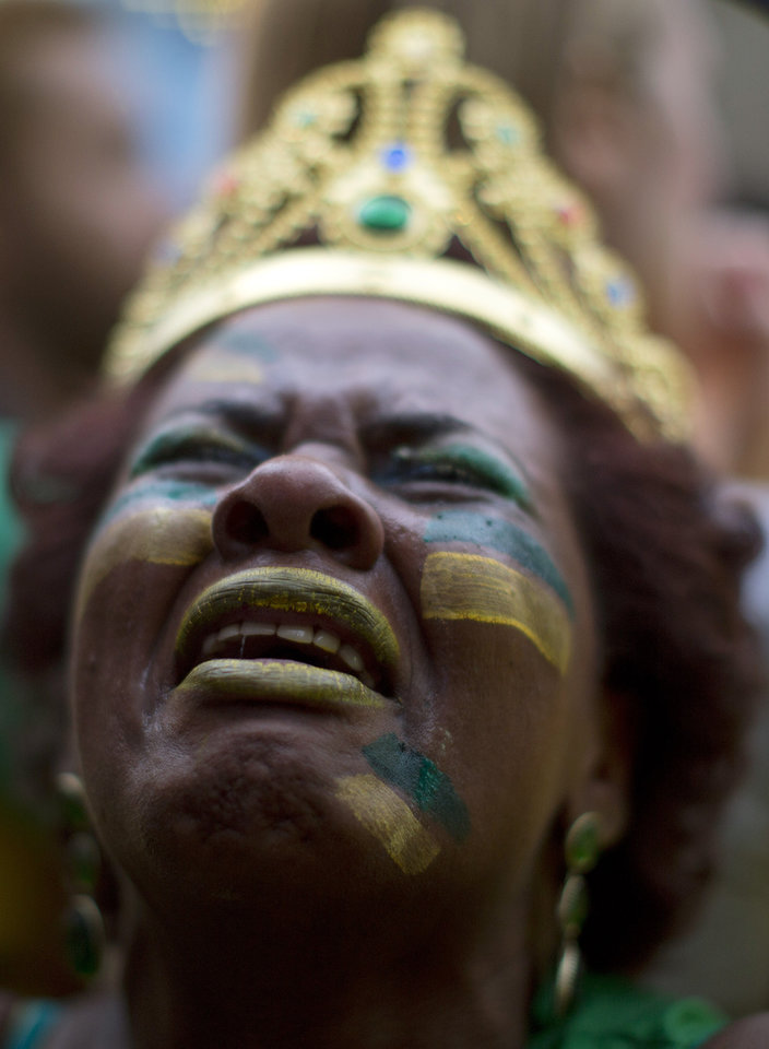 Photo - A Brazil soccer fan weeps as she watches Germany score repeatedly against Brazil at a World Cup semifinal match on a live telecast inside the FIFA Fan Fest area in Sao Paulo, Brazil, Tuesday, July 8, 2014. (AP Photo/Dario Lopez-Mills)