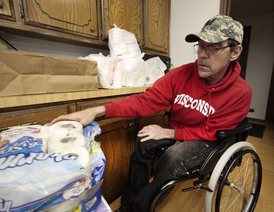 Photo - Members of the Memorial Baptist Church in Fond du Lac, Wis.,  came to McLoud, Oklahoma to help at the food pantry at the Emmanuel Baptist Church. Cal Popp sorts rolls of toilet paper in the food pantry on Wednesday.  David McDaniel - The Oklahoman