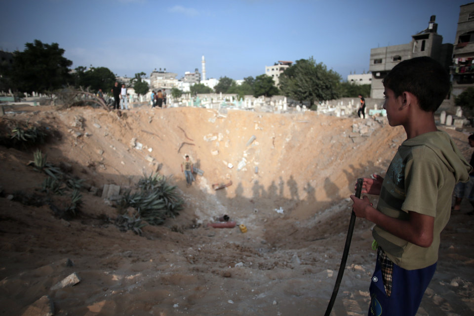 Photo - Palestinian check a crater caused by an Israeli strike at a cemetery in the Jabaliya refugee camp, northern Gaza Strip, Monday, July 28, 2014. Monday marked the beginning of the three-day Eid al-Fitr holiday, which caps the Muslim fasting month of Ramadan. Muslims usually start the day with dawn prayers and visiting cemeteries to pay their respects to the dead, with children getting new clothes, shoes and haircuts, and families visiting each other. (AP Photo/Khalil Hamra)