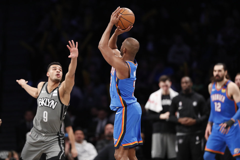 Photo - Brooklyn Nets guard Timothe Luwawu-Cabarrot (9) defends as Oklahoma City Thunder guard Chris Paul (3) shoots for three points during the second half of an NBA basketball game, Tuesday, Jan. 7, 2020, in New York. The Thunder defeated the Nets 11-103 in overtime. (AP Photo/Kathy Willens)