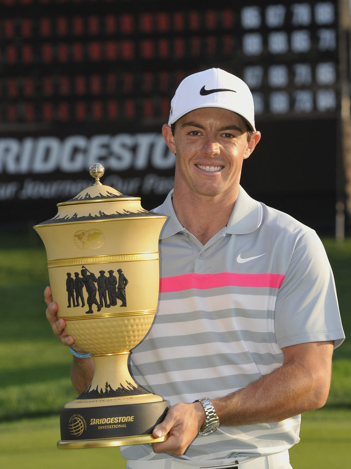 Photo - Rory McIlroy, of Northern Ireland, poses with the championship trophy after winning the Bridgestone Invitational golf tournament, Sunday, Aug. 3, 2014, in Akron, Ohio. McIlroy won with a final round 66 to beat Sergio Garcia by two strokes. (AP Photo/Phil Long)