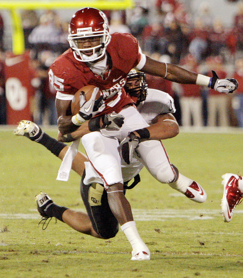 Photo - OU's Ryan Broyles (85) is tackled by Liloa Nobriga (48) of Colorado in the first quarter during the college football game between the University of Oklahoma (OU) Sooners and the University of Colorado Buffaloes at Gaylord Family-Oklahoma Memorial Stadium in Norman, Okla., Saturday, October 30, 2010. Photo by Nate Billings, The Oklahoman