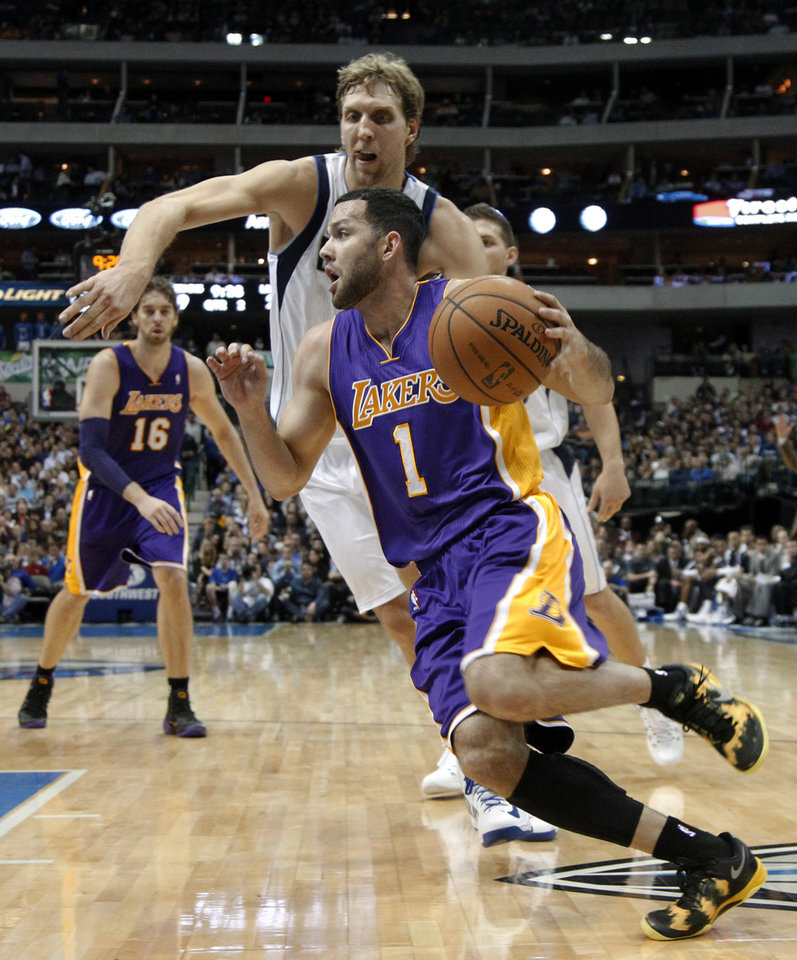 Photo - Los Angeles Lakers' Jordan Farmar (1) drives past Dallas Mavericks' Dirk Nowitzki, of Germany, for a shot attempt in the first half of an NBA basketball game, Tuesday, Nov. 5, 2013, in Dallas. Lakers' Pau Gasol (16), of Spain, watches from the rear. (AP Photo/Tony Gutierrez)