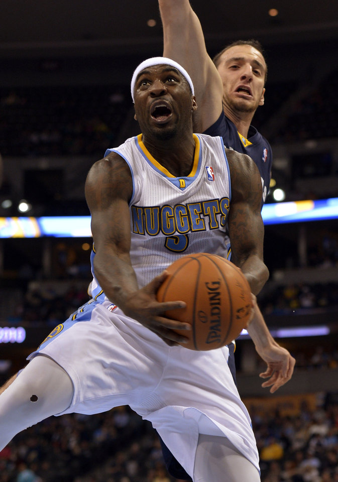 Photo - Denver Nuggets guard Ty Lawson, front, goes up for a shot against Memphis Grizzlies center Kosta Koufos during the third quarter of an NBA basketball game on Monday, March 31, 2014, in Denver. (AP Photo/Jack Dempsey)
