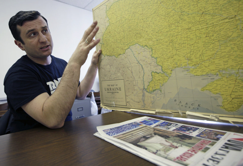 Photo - Sergiy Bondin, 37, of Stryy a town near Lviv, in western Ukraine, holds a map of his country at the Ukrainian National Home, a Ukrainian community association, Wednesday, Feb. 19, 2014, in New York. Bondin said his wife, who is currently in Ukraine, told him that men from their home town are trying to block the main road between Lviv and Kiev to prevent police from going to Kiev to deal with the protesters there. Bondin said some police in Western Ukraine, which was the first town to support the Ukrainian nationalist movement during the breakup of the Soviet Union in 1990, are starting to side with the protesters. (AP Photo/Kathy Willens)