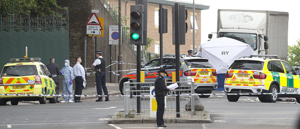 Photo - Police and forensic officers near the scene of an attack which has left one man confirmed dead and two people wounded near Woolwich barracks in London Wednesday, May, 22, 2013. Scotland Yard said officers responded to reports of an assault Wednesday afternoon in the London neighbourhood of Woolwich. London Ambulance service said one man was found dead at the scene and two other men were taken to the hospital, with one in serious condition.(AP Photo/Alastair Grant)