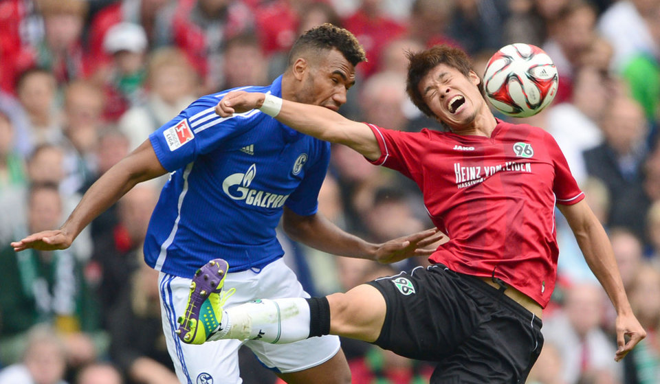 Photo - Hannover's Hiroki Sakai, right, challenges for the ball with Schalke's Eric Maxim Choupo-Moting, during the German Bundesliga soccer match between Hannover 96 and Schalke 04, in Hannover, northern Germany, Saturday Aug. 23, 2014.   (AP Photo/dpa,Peter Steffen)