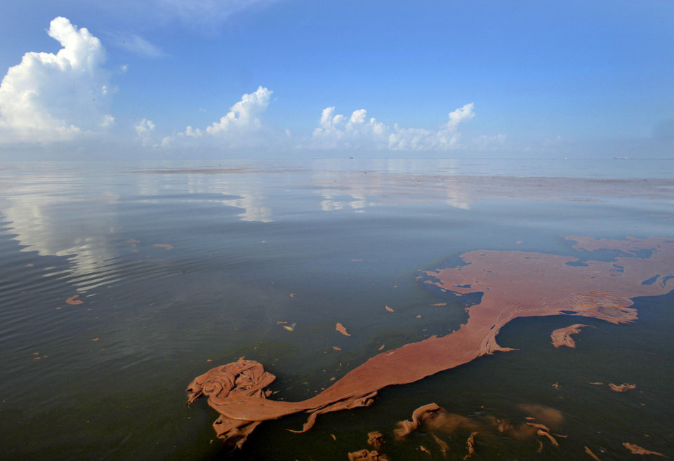 Photo - FILE - Oil from the Deepwater Horizon spill floats on the water as the sky is reflected in sheen on Barataria Bay, off the coast of Louisiana, in this June, 7, 2010 file photo. A high-stakes trial to assign blame and help figure out exactly how much more BP and other companies should pay for the spill began Monday, Feb. 25, 2013. (AP Photo/Charlie Riedel, File)
