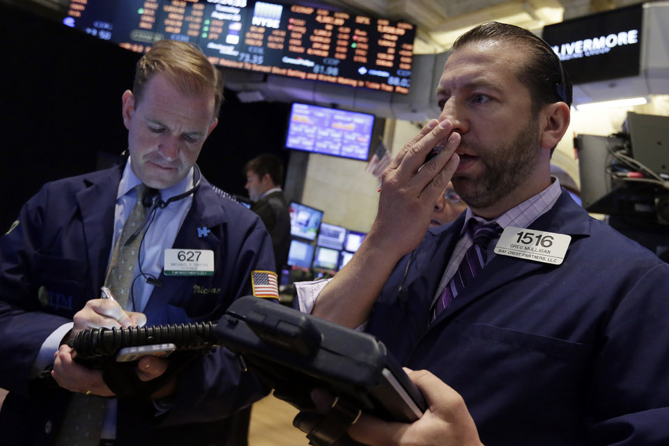 Photo - Traders Michael Smyth, left, and Greg Mulligan work on the floor of the New York Stock Exchange, Tuesday, Aug. 5, 2014. U.S. stock prices are opening lower as traders digest some mixed corporate earnings and a weak indicator on the Chinese economy. (AP Photo/Richard Drew)